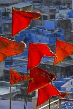 Saffron-Coloured Triangular Flags Flying on Flag Poles in Front of Blue Houses