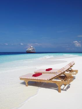 Lounge Chairs on Beach and Yacht, Maldives, Indian Ocean, Asia by Sakis Papadopoulos