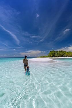Woman with snorkelling gear on tropical beach, The Maldives, Indian Ocean by Sakis Papadopoulos