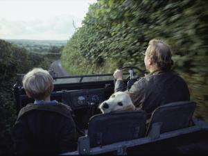 A Man and His Son and Dog Drive Down a Country Road Near their Home by Sam Abell