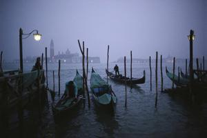 Gondoliers ready their boats for the night at a gondola yard off the San Marco Canal. by Sam Abell