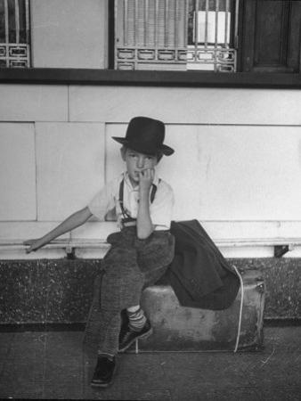 Little Boy Sitting on His Luggage While Waiting For the Train at the Denver Union Station by Sam Shere