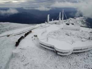 A Cog Railway Carries Visitors to the Top of the Snow Covered Peak by Sandy Felsenthal