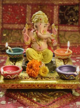 A Statue of a Mythological Elephant God -Ganesha, Surrounded by Traditional Divali Lamps by satel