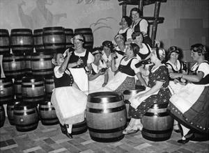 Junge Frauen in Tracht trinken an einem Messestand Bier, 1934 by Scherl