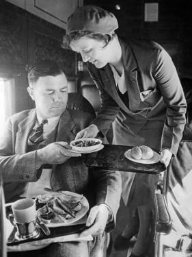 Stewardess Serving Dinner Aboard an Airplane, 1932 by Scherl Süddeutsche Zeitung Photo
