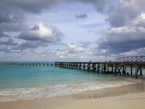 Jetty on Cancun Beach, with Grey Clouds Overhead by Sean Caffrey