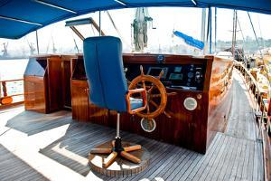 Cockpit inside a Boat with a Wood Wheel and Leather Chair. by Selenka