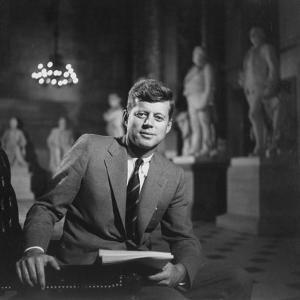 Senator John F. Kennedy Seated in Museum W. Statues