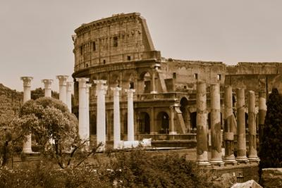 Sepia image of columns of the Forum and Colosseum or Roman Coliseum at dusk with streaked car li...