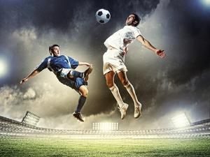 Two Football Players in Jump to Strike the Ball at the Stadium by Sergey Nivens