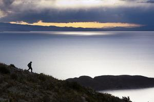 A Man Walks Along a Rocky Crest Above Lake Titicaca in Bolivia During Sunset by Sergio Ballivian