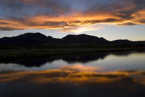 A Sunset over the Rocky Mountains Is Reflected in a Lake Near Boulder, Colorado by Sergio Ballivian