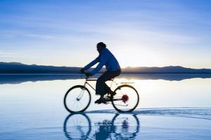 A Young Woman Rides Her Mountain Bike on the Flooded Salt Pan of the Salar De Uyuni in Sw Bolivia by Sergio Ballivian