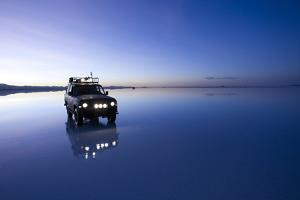 Travelers Drive their Suv across a the Salar De Uyuni, a Flooded Salt Flat, in Bolivia by Sergio Ballivian