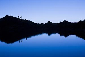 Trekkers are Reflected in the Cool Waters of Chilata Lagoon Outside the Town of Sorata, Bolivia by Sergio Ballivian