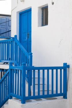 A Bright Blue Door and Stairway Railing on a White-Washed Building by Sergio Pitamitz