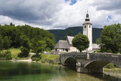 The church of St. John the Baptist and the stone bridge on Lake Bohinj, Slovenia, Europe by Sergio Pitamitz