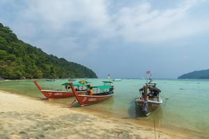 Three long tailed boats on a sandy beach, Thailand by Sergio Pitamitz