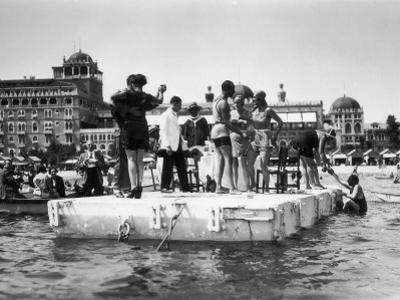 Several Young Men and Women on a Platform in the Water, Some of Them Dancing, on the Lido of Venice