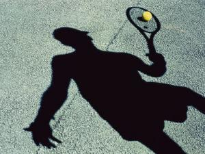Shadow of a Male Tennis Player Playing Tennis