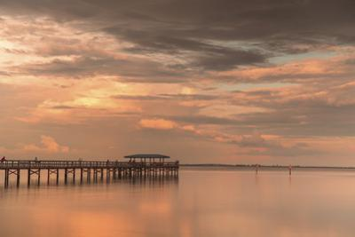 Fishing pier off Safety Harbor, Florida at sunset with people fishing, deep pink sunset sky by Sheila Haddad