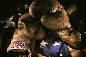 Pair of vintage boxing gloves laying on a flag carefully painted with light by Sheila Haddad