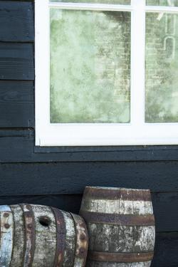 Rustic Barrels Lined Up Along an Old House Below a Window by Sheila Haddad