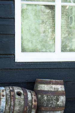 Rustic Barrels Lined Up Along an Old House Below a Window by Sheila Haddad