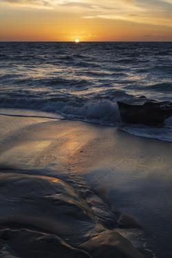 Sun setting on the Pacific Ocean with reflection of golden in the sand by Sheila Haddad