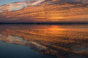 Sunrise Highlighting the Clouds Causing Dramatic Sky and Reflections by Sheila Haddad