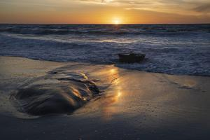 Sunset reflecting off the water on the sand of a beach by Sheila Haddad