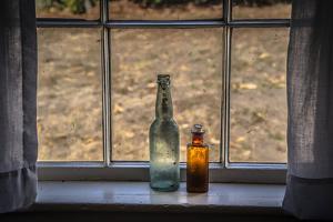 Two vintage bottles on window sill. by Sheila Haddad
