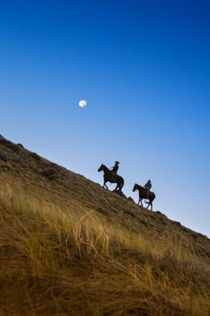 Two wranglers riding horses up a hill with full moon in background at blue hour by Sheila Haddad
