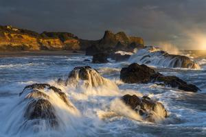 Waves crashing on rocks and washing down the sides at sunset by Sheila Haddad