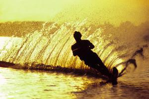 Silhouette of a man waterskiing in sea