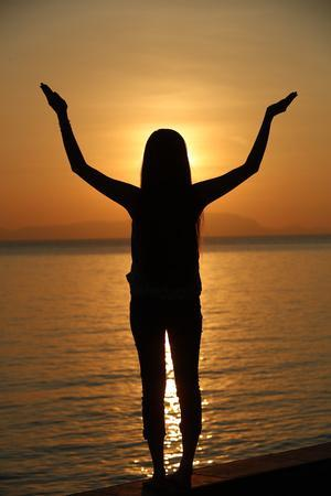 https://imgc.allpostersimages.com/img/posters/silhouette-of-a-woman-standing-by-the-sea-at-sunset-doing-yoga-pose-and-meditation-kep-cambodia_u-L-Q1GYKQW0.jpg?artPerspective=n