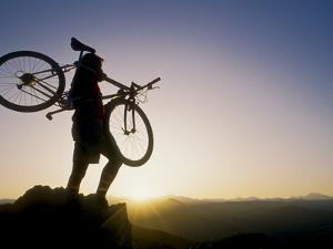 Silhouette of Mountain Biker at the Summit During Sunrise