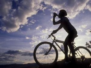 Silhouette of Mountain Biker Drinking at the Summit During Sunset