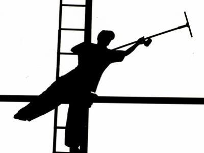 Silhouetted against the Bright Morning Sun, a Window Cleaner Stretches to Clean a Spot