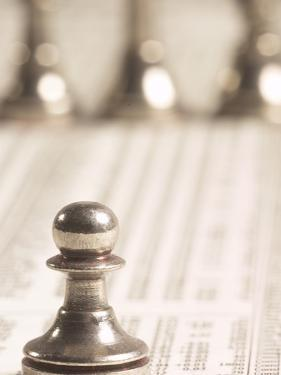 Silver Pawn on Newspaper Stock Market Report with Line of Chess Pieces
