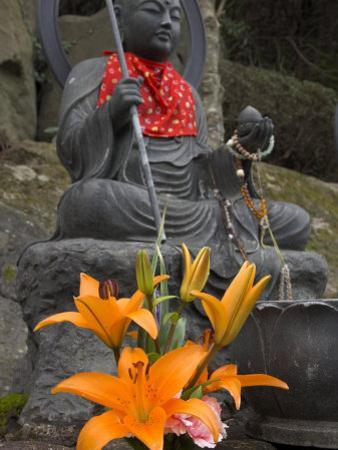 Buddha with Red Scarf and Fresh Flowers, Daisho in Temple, Miyajima, Honshu, Japan by Simanor Eitan