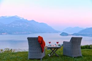 Armchairs and red wine with views of Lake Como at sunset, Lombardy, Italian Lakes, Italy by Simon Montgomery