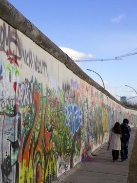 Couple Walking Along the East Side Gallery Berlin Wall Mural, Berlin, Germany, Europe by Simon Montgomery