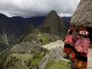 Traditionally Dressed Children Looking over the Ruins of Machu Picchu, UNESCO World Heritage Site,  by Simon Montgomery