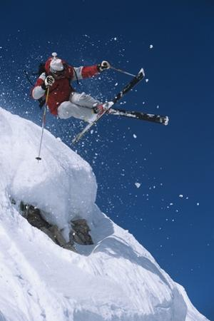 Skier in Mid-Air Above Snow on Ski Slopes