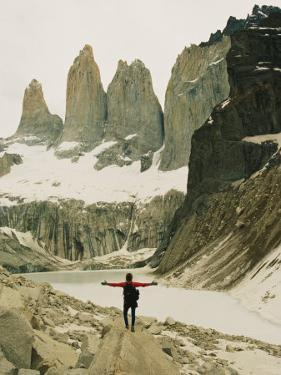 A Hiker with Outstretched Arms is in Awe of the Jagged Landscape by Skip Brown