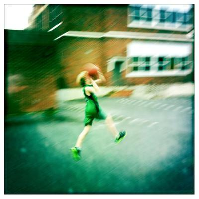 A Ten Year Old Boy Drives to the Basket on a School Playground by Skip Brown