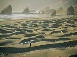 A Windsurfer Walks Across the Sand Dunes Near the Rocky Coastline by Skip Brown