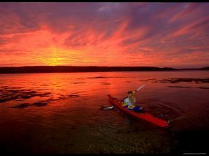 A Woman Paddles a Sea Kayak at Dusk by Skip Brown